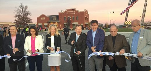 Mayor Brainard, center, and other city officials cut the ribbon celebrating Carmel's 100th roundabout. (Photo by Adam Aasen)