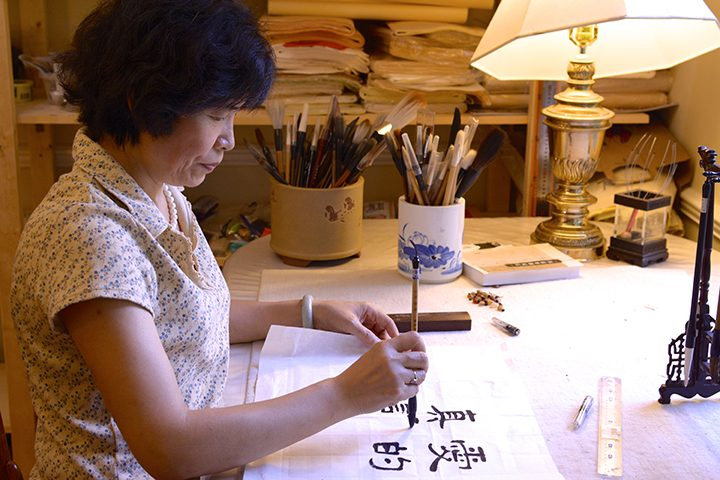 Jenny Feng practices calligraphy in her Carmel home. (Photos by Lisa Price)