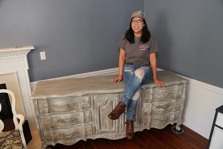 Meaghan Wolf rests on a piece of furniture she refinished in her Carmel home. (Photo by Ann Marie Shambaugh)