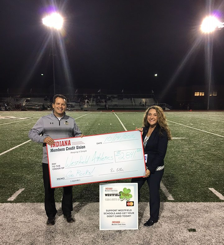 The Indiana Members Credit Union contributed $2,841 to Westfield High School last month in part with an ongoing school spirit debit card program. Westfield fans can sign up for a Rocks-themed debit card, and each time the card is used, Westfield athletics benefit from the transaction. Athletic Director Bill Davis, left, receives the check from Gina Terril, IMCU senior business development officer. (Submitted photo)