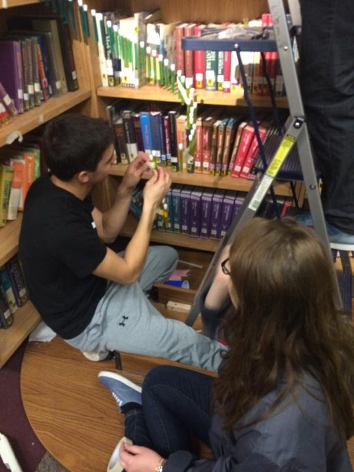 Sharon Hoffman and Justin Mamaril construct a chandelier out of test tubes to follow the Fibonacci spiral and hung it in the Westfield High School library. (Submitted photo)