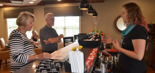 Holly Miller, owner of Black Acre Brewing Co. and clinical director for Freedom Home Health, serves beer samples to event attendees Janet Kuebler and Ted Richey. (Photo by Sara Baldwin)