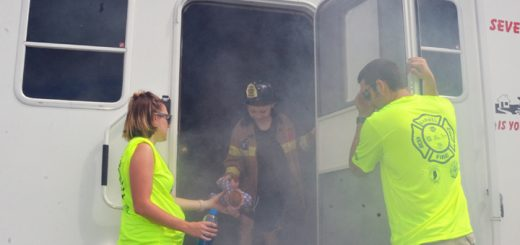 A trailer is set up to mimic a burning house. Zahar Rush exists the house, helped by firefighter Grant Russel and his wife, Lauren Russel, both volunteers. (Photo by Sara Baldwin)
