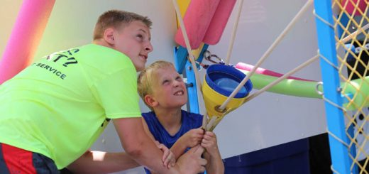 Kris Bendt, left, helps Will Doan launch a water balloon at the Water Wars game in the kids area. (Photo by Ann Marie Shambaugh)