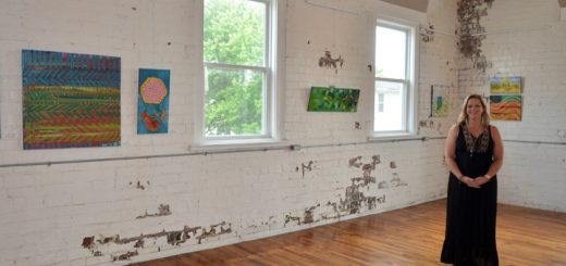 """Salewicz in the main gallery at Sugar Creek Art Center, amongst her """"Rural Routes"""" pieces. (Photo by Sara Baldwin)"""