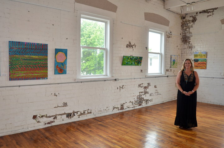 "Salewicz in the main gallery at Sugar Creek Art Center, amongst her ""Rural Routes"" pieces. (Photo by Sara Baldwin)"