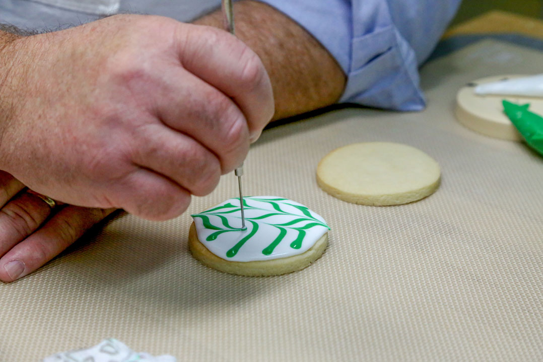 Dave Sanders of Poppy and Sweetpea's Cookies uses a wet-on-wet technique to decorate a sugar cookie in the commercial kitchen in his Carmel home. (Photo by Ann Marie Shambaugh)