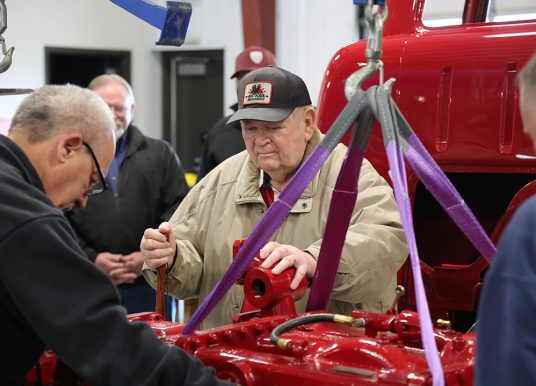 Man who originally installed pump on Carmel fire engine helps lower it back in place during restoration