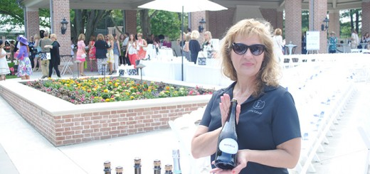 "Terri Scritchfield poses with a wine bottle as she serves those who attended the ""Wine, Women & Shoes Benefit.""  Scritchfield served wine throughout the event. ""I am serving [wine], said Scrithfield, ""I work for the Lucas [Oil] Estate. We do lots of fundraisers [and] special events."