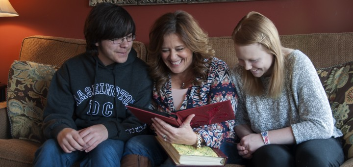 Nick, Melissa and Isabella Shelton, who hope birth records will be open to adopted kids, look at family photos. (Photo by Heidi Schmidt)