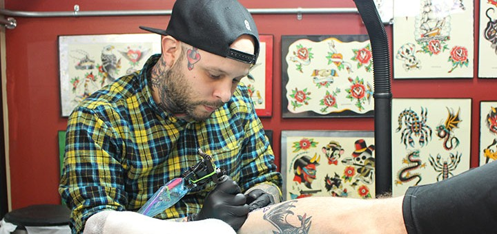 Aldo Rodriguez works on a leg tattoo. (Photo by James Feichtner)